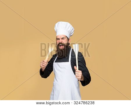 Bearded Cook With Wooden Spoon And Spatula In Hand. Cooking. Bearded Man Preparing To Cook Food. Han