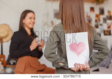 Girl Holds A Card Made For Mom On Holiday Behind Her Back.
