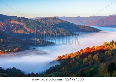 Beautiful Autumn Landscape With Valley Fog. Wonderful Nature Scenery At Sunrise. Mountain Ridge In T