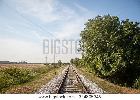 Abandoned Railway Track, On A Defunct Line In Serbia, Europe, Rusty, Surrounded By Trees And A Rural