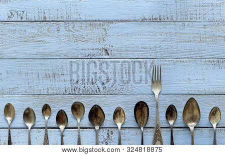 Vintage Cutlery - Spoons, Forks And Knives On An Old Wooden Background. Selective Focus.