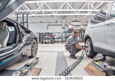 Car Repair, Bmw Advertising, Moscow, 1.11.2018: Car Repair: Wheel Replacement Closeup. Mechanic Scre