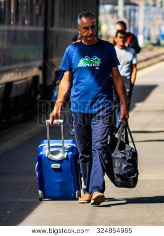 Man Walking Alone Carrying Luggage And Waits Train On The Platform Of Bucharest North Railway Statio