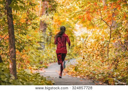 Run woman jogging in outdoor fall autumn foliage nature background in forest. Trail running runner athlete training cardio outdoors, orange colors tree leaves.