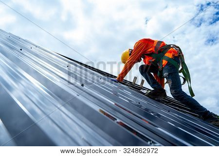 Roofer Working On Roof Structure Of Building On Construction Site,roofer Using Air Or Pneumatic Nail