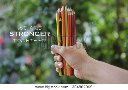 Inspiratinal motivational quote - We are stronger together. With young woman hand holds bunch of pencil colored and blurry green garden background. Togetherness concept. poster