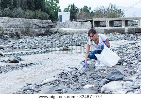 Stock Photo Of A Girl With Blue Gloves Crouched On The Bank Of The River Picking Up A Plastic Bottle