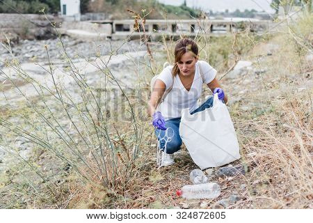 Stock Photo Of A Girl With Blue Gloves Crouched On The Bank Of The River Collecting Plastic. Recycli