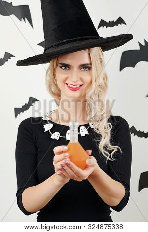 Portrait Of Smilng Pretty Sorceress With Ghost Necklace Holding Bottle Of Magic Potion And Lookig At