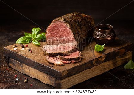 Juicy Roast Beef With Spices Sliced On A Cutting Board, Delicious Meat, Traditional Food. On Dark Ba
