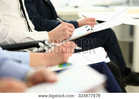 Focus On Smart Workers Hands Writing Something Down In Paper Folder With Great Concentration. Manage