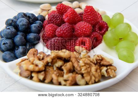 Healthy Nutrition, Berries And Nuts. Wild Strawberries, Grapes, Blueberries, Walnuts, Pistachios. Ec