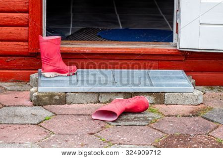 Wellies Lying In The Entrance Of The Wooden House