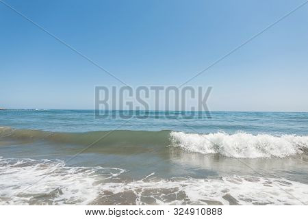 Blue Ocean With Waves With White Foam And Clear Blue Sky. Seascape. Spain. Sunny Day. Paradise.