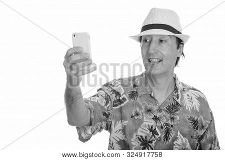 Studio Shot Of Happy Mature Man Smiling And Taking Selfie With Mobile Phone