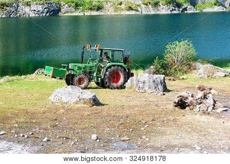 Tractor Pulling Away Fallen Tree Trunks