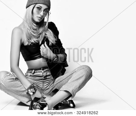 Portrait Of Young Grunge Blonde Woman In Torn Jeans, Top, Brutal Boots And Winter Hat Sitting Cross