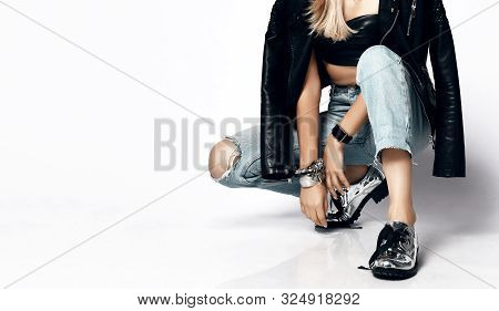 Closeup Portrait Of Young Grunge Woman In Torn Jeans, Leather Top, Leather Jacket And Chrome Brutal