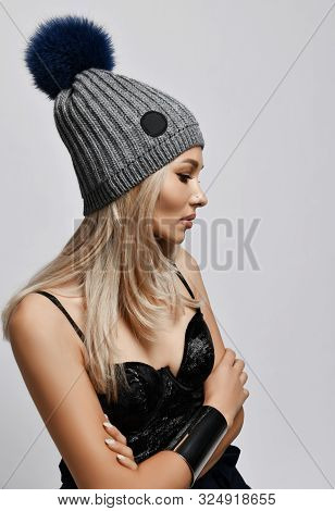 Portrait Of Glamour Blonde Woman In Plush Top Bra And Grey Winter Hat With Big Furry Pompon Standing