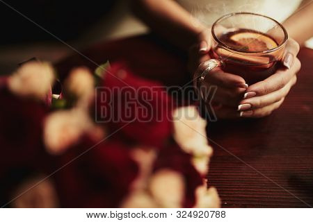 Young Bride Drinking Tea. Wedding Bouquet On A Wooden Table In A Restaurant. Cropped Image Of Bride
