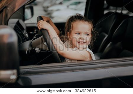 A Little Girl With Long Hair Is Sitting At The Wheel Of A Car. Happy Childhood, Young Driver, Travel