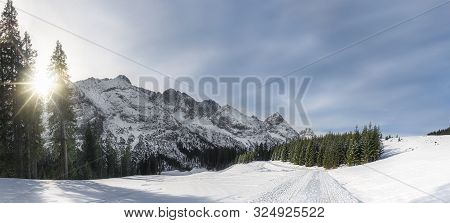 Sunny Winter Panorama With Majestic Snow-capped Alps Mountain Peaks, Snowy Road, And Snow-covered Tr