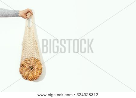 Hand Is Holding A Pumpkin In A Shopping Bag, Front View, Autumn Sale Concept, Copy Space For A Text