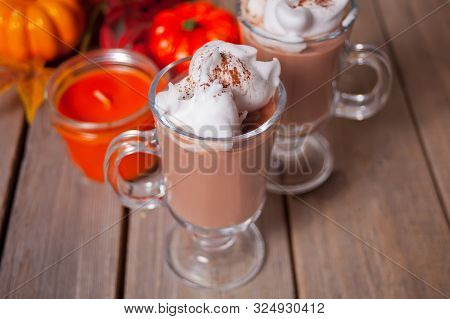 Two glass of hot creamy cocoa with froth with autumn leaves and pumpkins on the background poster