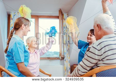 Seniors training fitness and coordination with cloth gymnastics in nursing home