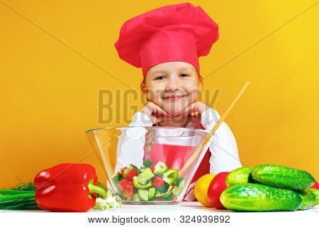 Beautiful Little Girl Chef Cook On A Yellow Background. A Child Is Preparing A Vegetable Salad.
