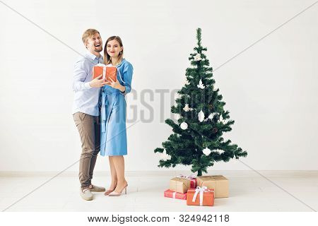 Holidays And Celebrations Concept - Cute Young Couple Exchanging Christmas Presents In Front Of A Ch