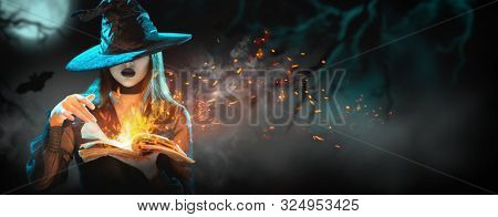 Halloween Witch girl with magic Book of spells portrait. Beautiful young woman in witches hat conjuring, making witchcraft. Over spooky dark magic forest background. Wide Halloween party art design.