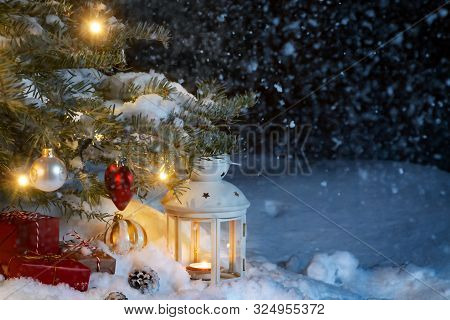 Christmas Composition - Gifts And A Lantern In The Snow Under A Christmas Tree Decorated With Lights