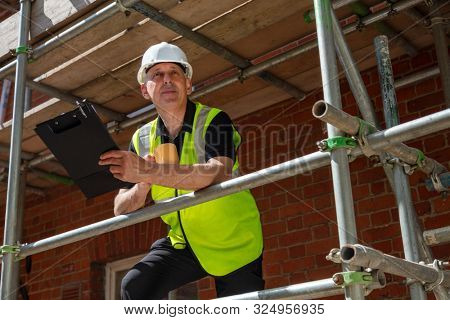 Male builder foreman, construction worker or site manager holding a clipboard, wearing a white hard hat and hi vis vest drinking mug of tea or coffee