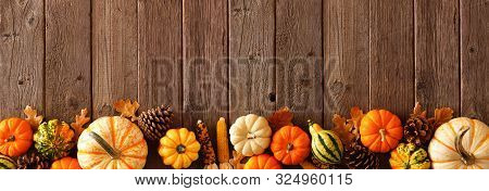 Autumn Bottom Border Banner Of Pumpkins, Gourds And Fall Decor On A Rustic Wood Background With Copy