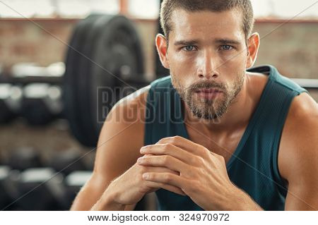 Young muscular man resting in gym while looking at camera. Portrait of competitive sportsman at wellness center. Determined sweaty guy taking a break after working out session with copy space.