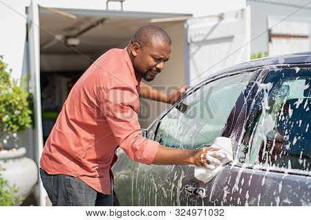 Middle aged black man cleaning his car outside the garage in the driveway. Mature african man cleaning automobile with sponge at car wash. Casual guy washing car with sponge and foam.