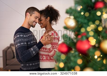 Romantic multiethnic couple holding hands and dancing near christmas tree at home. Loving boyfriend and african girlfriend embracing with love at christmas holidays. New year's eve.