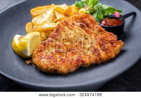 Fried Wiener schnitzel from veal topside with French fries and lettuce as closeup on a modern design plate