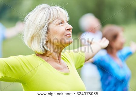 Active seniors in a yoga class do a breathing exercise for relaxation