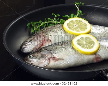 Trout with rosemary and lemon slices on frying pan poster
