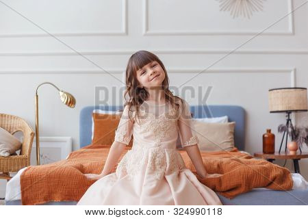 Cute Little Child Girl Sitting On Bed
