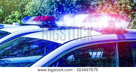 Police Lights On Car During Traffic Surveillance On The City Road. Flash Light On The Vehicle Of The