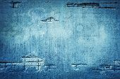 Concrete devastated blue wall with visible rebar. poster