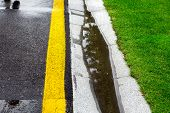 the current rainwater in the filled canal is a cement ditch of the drainage system on the side of a wet asphalt road after rain, background on the topic of environmental safety. poster