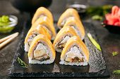 Macro shot of tropical sushi rolls with banana, eel, rice, cream cheese and processed cheese on black background. Eating fusion uramaki sushi with selective focus closeup in Japanese restaurant poster