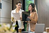 Two asian businesswomen discussing with the partner business about business contract by technology laptop in modern meeting room, office or working space, coffee break, partner and colleague concept poster
