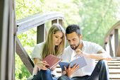 Beautiful couple reading book outdoors poster