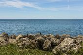 Beautiful nature landscape view. Rocky coast line.  Blue water surface of Atlantic ocean merging with blue sky. Key West, Florida. poster