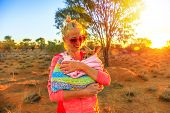 Tourist woman holding orphaned baby kangaroo at sunset sunlight in Australian outback. Interacting with cute kangaroo orphan. Australian Marsupial in Northern Territory, Central Australia, Red Centre. poster